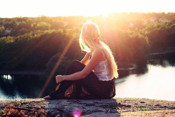 Junge Frau sitzend im Sonnenlicht