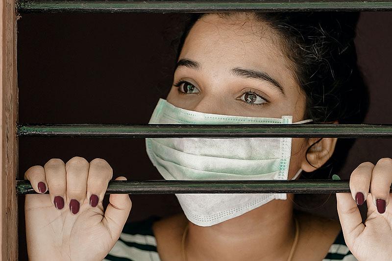 Frau hinter Gitter mit Maske